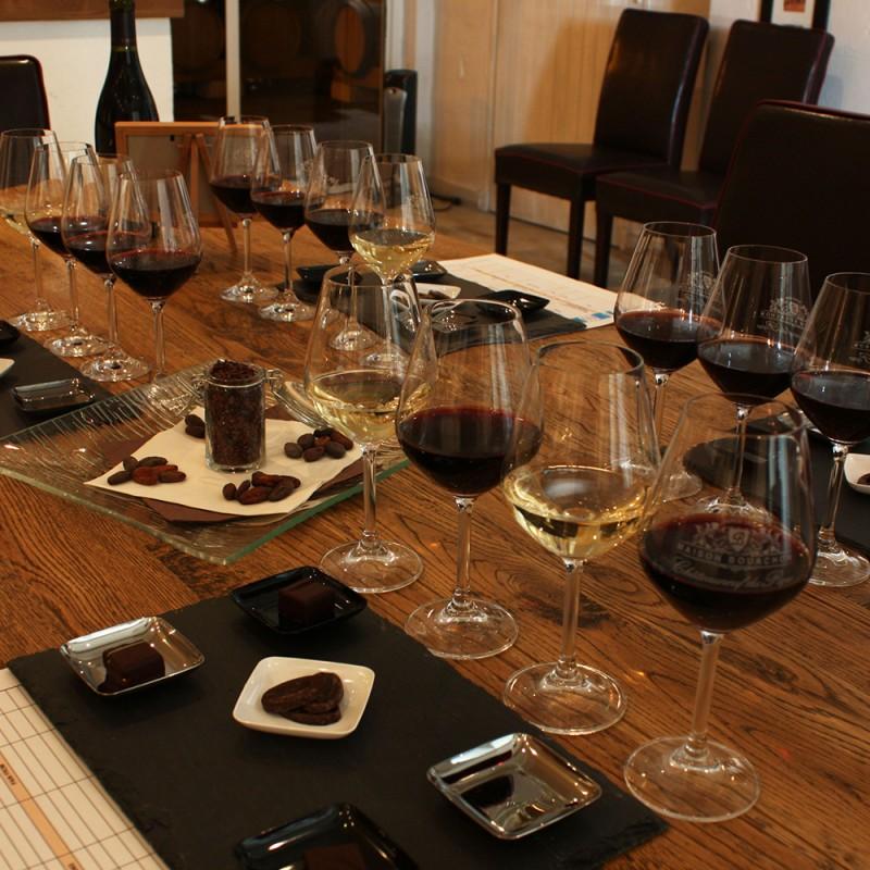dégustation de vins rouge et blanc accompagnés de chocolats sur une table en bois