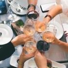 Plusieurs personnes trinquant avec un verre de vin